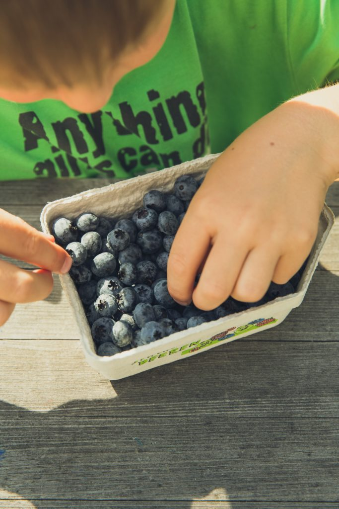 Child looking at blueberries
